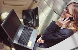 beautiful business woman sitting with laptop in rear compartement of limousine