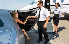 VIP guest arrives in limousine at airport and is greeted by pilot