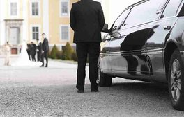 chauffeur standing next to black limousine in front of castle, waiting for bride and groom